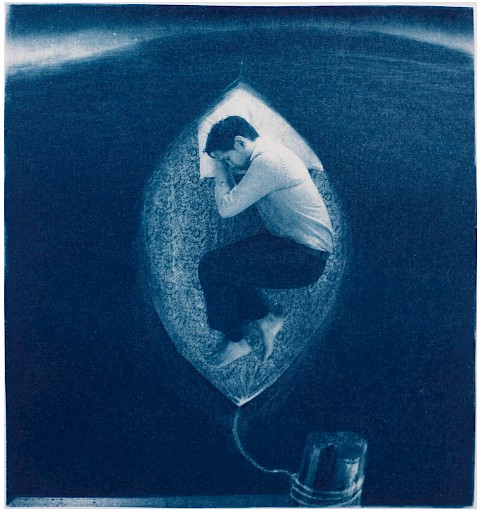 man sleeping on a leaf-like boat floating on water suggesting rebirth and being tied down by umbilical cord