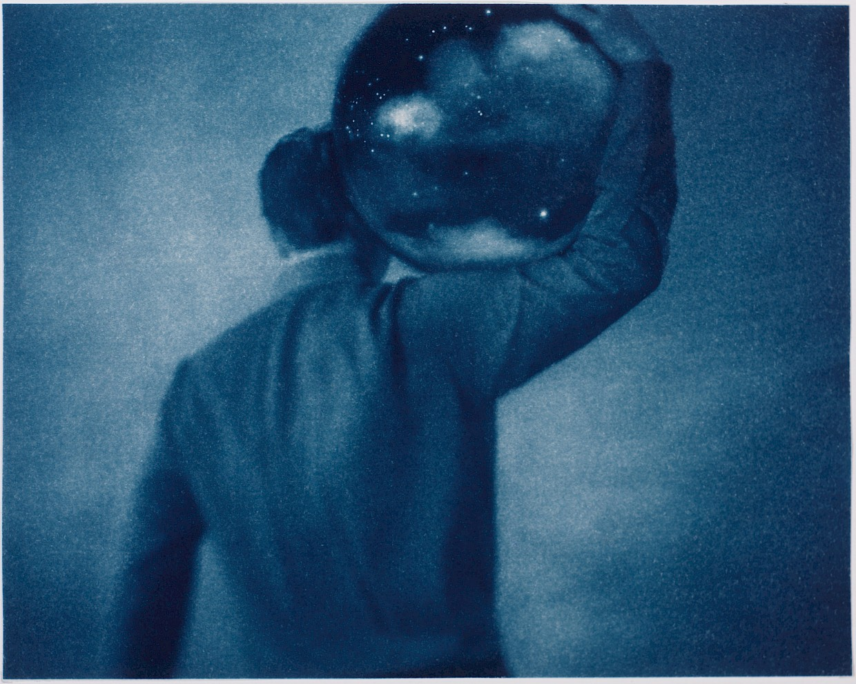 Man holding a globe containing the night sky and stars on his shoulders metaphor for man's search for meaning & purpose in life