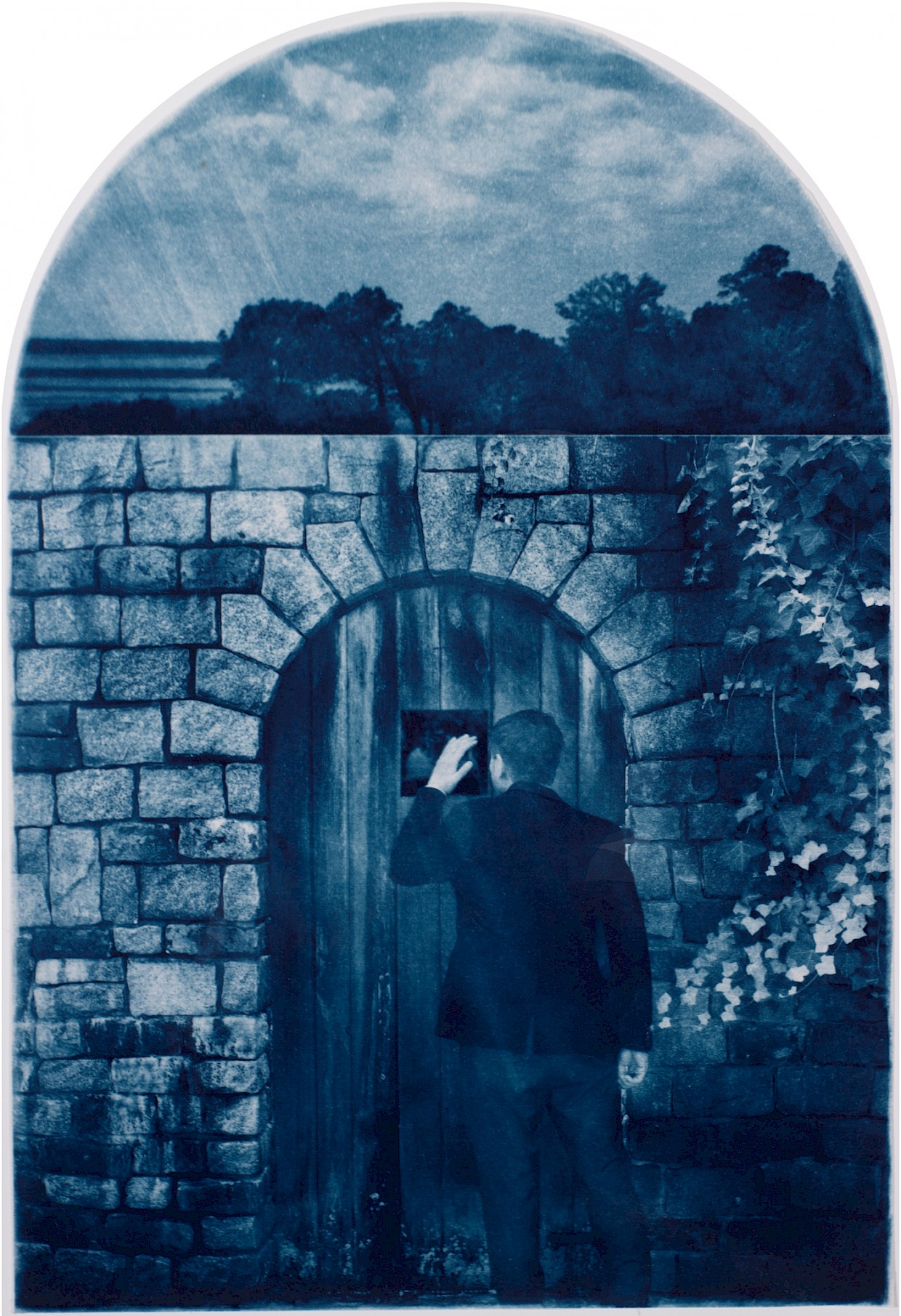 man in front of locked gate and he peers through a peep hole to the landscape beyond