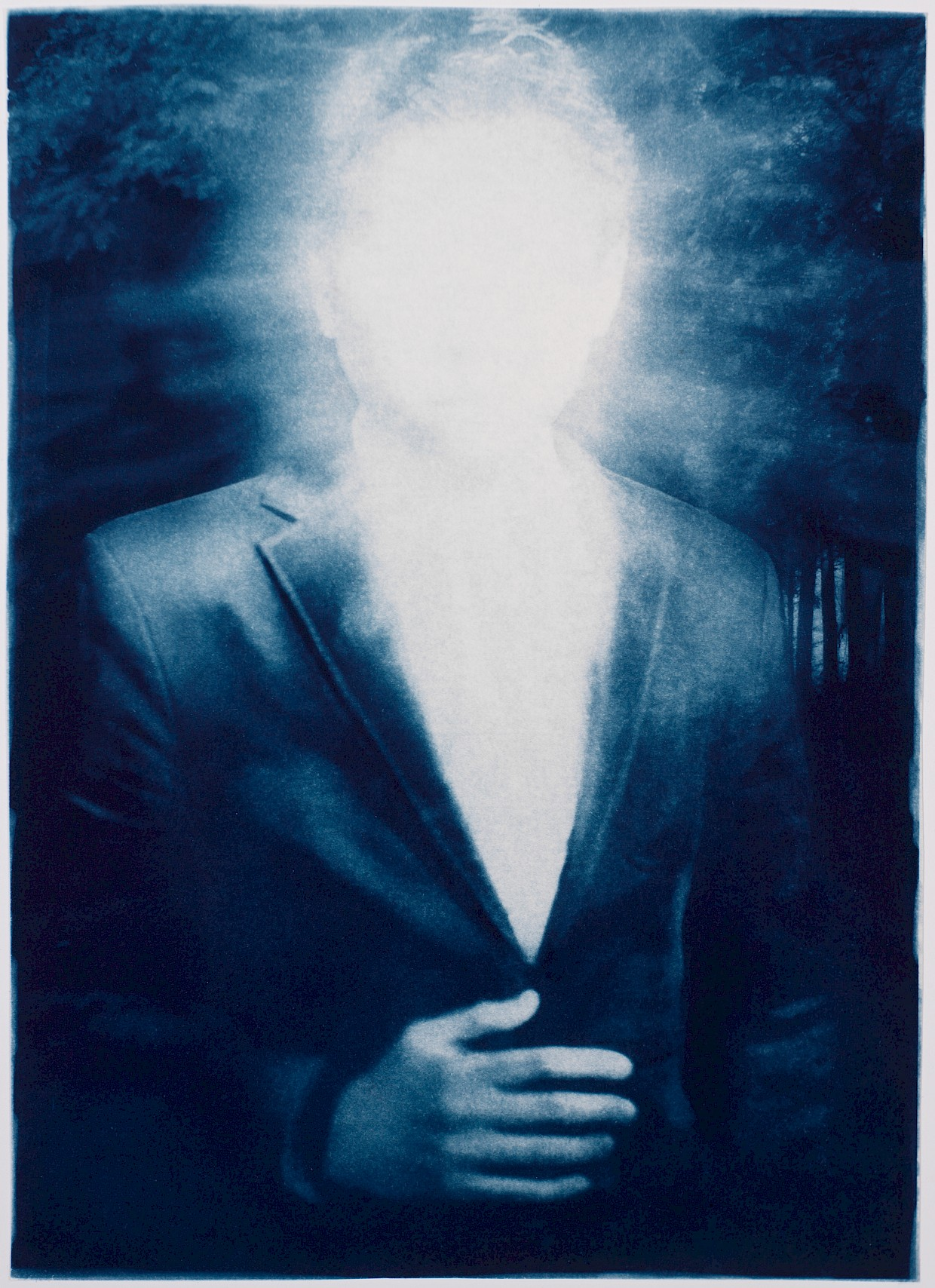 man in business suit with light emanating from his face suggesting enlightenment