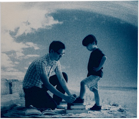 father tying shoes of son on the beach