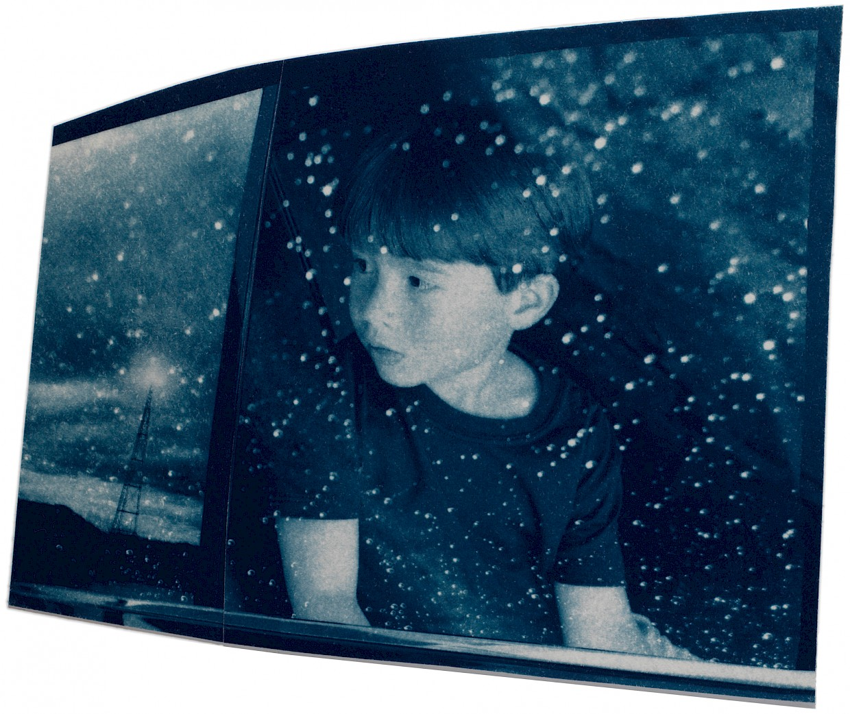 young boy looking outside of car window while it is raining