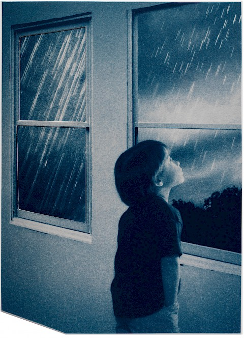 boy looking out window while it is raining