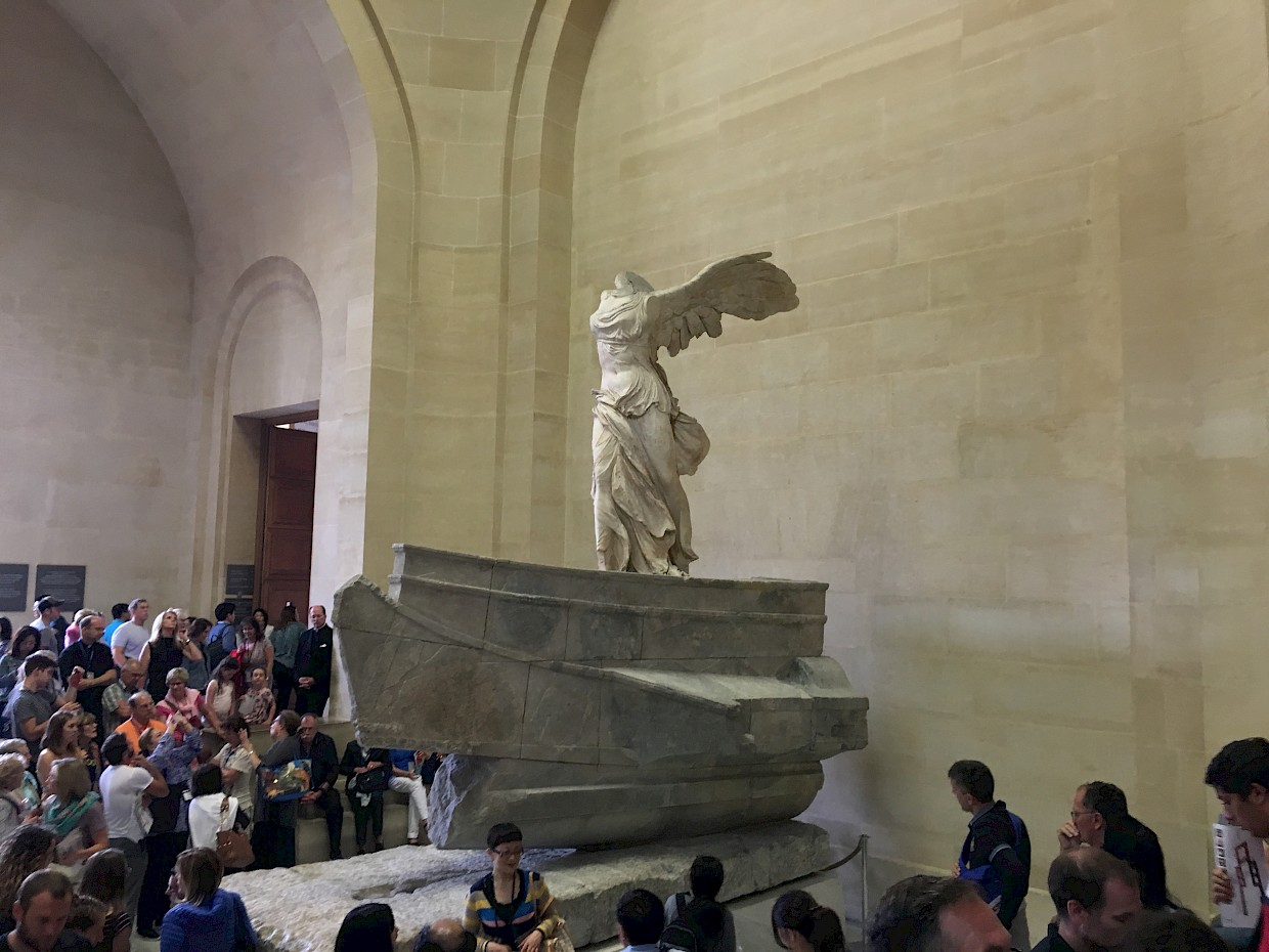 ancient sculpture of woman with angel wings onlookers around it at the Louvre