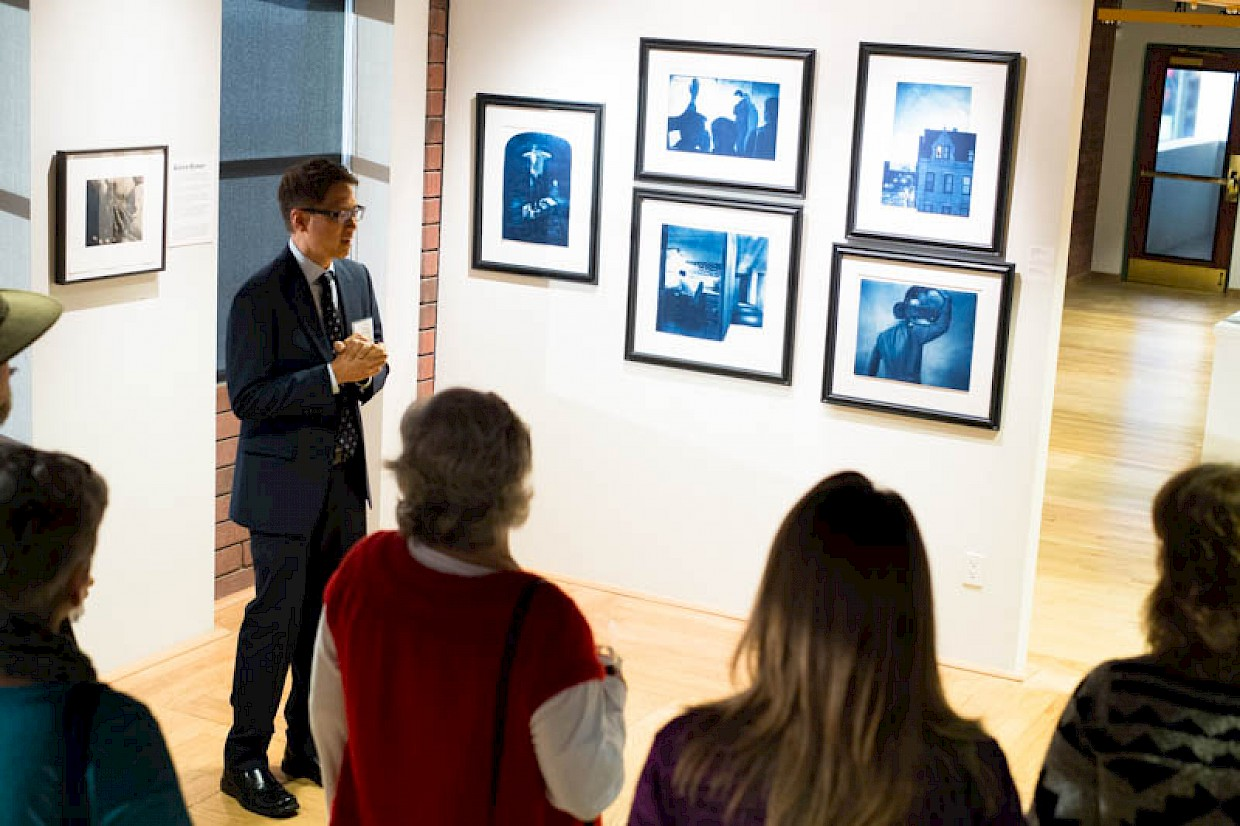 man talking about his cyanotype prints on display in exhibition