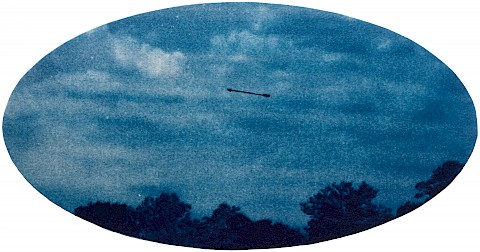 cyanotype image arrow against sky with trees in bottom